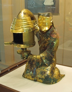 A gilded bronze oil lamp in the shape of a kneeling female servant, dated 2nd century BC, found in the tomb of Dou Wan, wife of the Han prince Liu Sheng; its sliding shutter allows for adjustments in the direction and brightness in light while it also traps smoke within the body.[17]