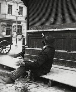 A man drinking from a bottle of liquor while sitting on a boardwalk, ca. 1905–1914. Picture by Austrian photographer Emil Mayer.
