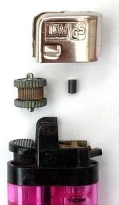 Газовая кремнёвая зажигалка с поджигом от огнива. Слева колесико кремня из закаленной стали, справа кусочек кресала из мишметалла.