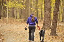A college student walks her dog at Lake Johnson in the Fall