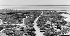 "Aerial view of Pan American Airways Hotel and facilities on Peale Island at Wake Atoll. The hotel is on the left, the anchor from the Libelle shipwreck and the pergola leading to the ""Clipper"" seaplane dock is on the right."
