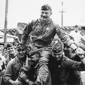 """Wolfpack"" aviators of the 8th Tactical Fighter Wing carry their commanding officer, Colonel Robin Olds, following his return from his last combat mission over North Vietnam, on 23 September 1967."