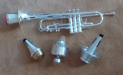"Trumpet with ""stonelined"" straight mute inserted. Below, left to right: straight, wah-wah (harmon), and cup mutes."