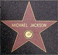 "Pink star with a gold colored rim and the writing ""Michael Jackson"" in its center. The star is indented into the ground and is surrounded by a marble-colored floor."