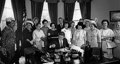 American Association of University Women members with President John F. Kennedy as he signs the Equal Pay Act into law in 1963