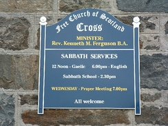 A sign indicating services in Gaelic and English at a Free Church of Scotland congregation in the community of Ness, Isle of Lewis