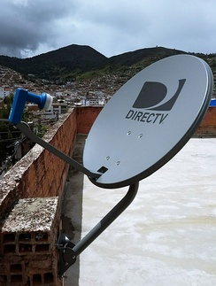 A standard DirecTV satellite dish with Dual LNB on a wall brick