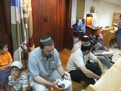 Worshipers seated on the floor of the synagogue before the reading of Lamentations on Tisha B'Av