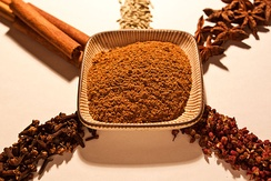 A common mix for ground five-spice powder (center) is (clockwise from top left) cinnamon, fennel seeds, star anise, Sichuan peppercorn and cloves