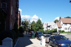 Southeastern portion of Austin Street with typical Queens six-story red brick apartment buildings on one side and residential homes on the other