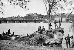 Black-and-white photo of several military men idling on a river bank. Across the river are several large buildings.