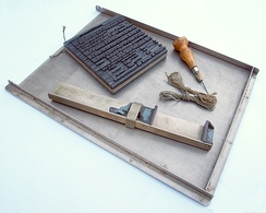 Tools for composing by hand: block of type tied up, a composing stick, a bodkin, and string, all resting in a type galley.