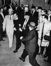 Ruby about to shoot Oswald, who is being escorted by Dallas police. Det. Jim Leavelle is wearing the tan suit. Det. L. C. Graves is wearing the dark suit. Ruby is approaching Oswald from the side, where he is unnoticed by anyone in the photograph.
