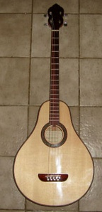Modern replica of a 1930s Lyon & Healy tenor guitar. Background tiles are 20cm square