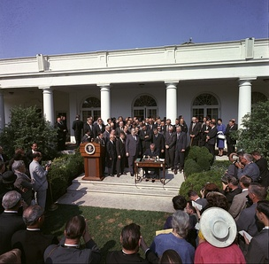 President Lyndon B. Johnson signs the Poverty Bill (also known as the Economic Opportunity Act) while press and supporters of the bill look on, August 20, 1964