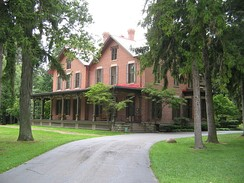 A large brick house surrounded by trees