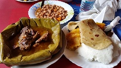 Ugandan traditional meal with Matoke steamed and served with luwombo, meat or groundnuts steamed in banana leaves.