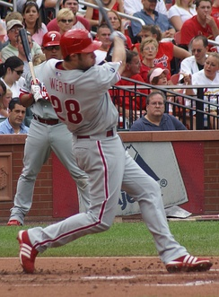 "A right-handed man in a gray baseball uniform with red trim and a red batting helmet swings at a baseball with a baseball bat. His jersey reads ""Werth"" and ""28"" on the back in red letters."