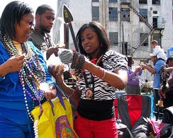 Revelers on Basin Street examine their parade catches, including a Zulu Coconut, 2009