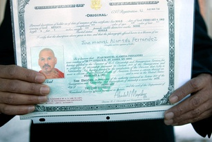 A person holding up their certificate of derivative citizenship.