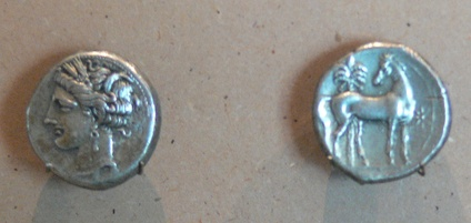 A silver Carthaginian shekel bearing the wreathed head of Tanit and a standing horse before a palm tree and beside a star.