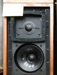 "A small LS3/5A ""bookshelf speaker"" with its protective cover removed."