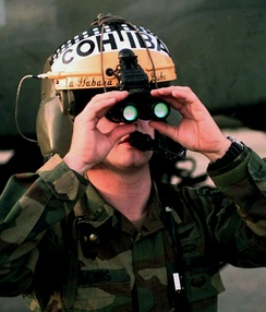 Binocular night vision goggles on a flight helmet. The green color of the objective lenses is the reflection of the light interference filters, not a glow.