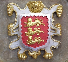 The college's coat of arms: the royal arms of the founder King Edward II within a bordure engrailed argent for difference. 16th/17th c.[43] roof boss with escutcheon in a strapwork frame on vault of main entrance