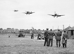 Personnel of No.121 (Eagle) Squadron look on as three Spitfire Vbs come in to land at RAF Rochford in Essex, after a fighter sweep over northern France during August 1942.