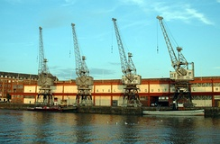 A long two-storey building with 4 cranes in front on the quayside. Two tugboats are moored at the quay.
