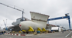 The bow section of Prince of Wales is delivered to Rosyth Dockyard in May 2014; the ship's sister Queen Elizabeth is in the dry dock behind