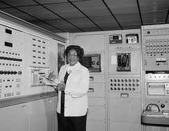 Black and white photograph of Mary Jackson standing in front of large instruments, holding a clipboard and pencil