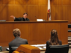 A trial in California. The judge is seated at the front of the room.