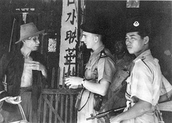 Police officers question a civilian during the Malayan Emergency.