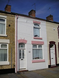 A colour photo of a white and pink cladded house