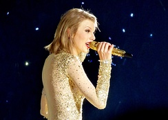 Swift performing on The 1989 World Tour. She is seen in bob hair and a sparkling bodysuit while grabbing a golden microphone