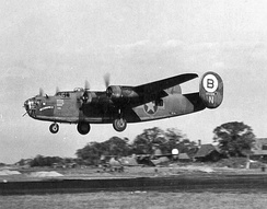 "329th Bomb Squadron B-24D-5-CO 41-23809 ""Hellsadroppin' II"", landing at RAF Hardwick 21 December 1943. This plane was declared 'War Weary' and transferred to the 448th Bomb Group to be used as its formation assembly ship and was carried three different names during its time there and was painted with a black and yellow checkerboard pattern over the whole plane. Photo taken 15 December 1943. She was condemned as salvage on Jan. 15,1945."
