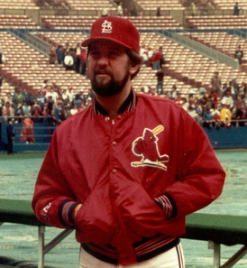 A bearded man with his hands in his jacket pocets, wearing a red baseball cap and red jacket with a bird logo on the left chest, standing with a field and stands in the background.