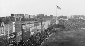 "The original ad-covered Green Monster in 1914, with ""overflow"" fan seating in front of the wall's base, atop ""Duffy's Cliff"" (seen in the distance, nearest the flagpole)."