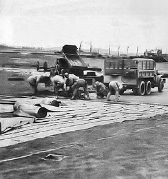 IX Engineering Command putting down a Pierced Steel Planking (PSP) Runway at an Advanced Landing Ground under construction