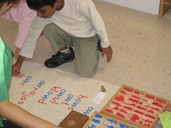 Children working with a moveable alphabet at a Montessori school[1]