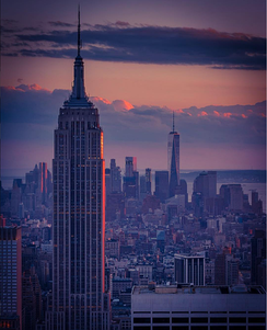 View of the Empire State Building southward from the top of Rockefeller Center, with One World Trade Center in the background, at sunset