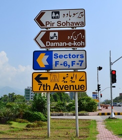 A bilingual Pakistani road sign showing the use of both Eastern Arabic and Western Arabic numerals. The propensity towards Western Arabic numerals can be clearly seen.