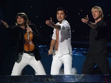 Dima Bilan performing at the Eurovision Song Contest final in Belgrade, 2008. He is accompanied by Edvin Marton (left) and Evgeni Plushenko (right).