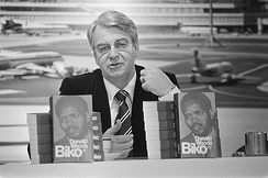A black and white photograph of a middle-aged white man. He has grey hair and is wearing a black suit and tie. He is sitting at a table, and in front of him are two upright books; both feature the face of Steve Biko, a young black man.