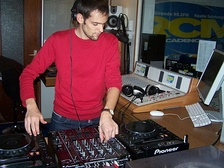 DJ Aron Scott DJing a set for a French radio station. He is using digital CDJ decks instead of phonograph turntables.