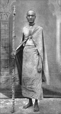 A photo of a standing Hindu monk in spectacles, with a shaved head and holding a staff