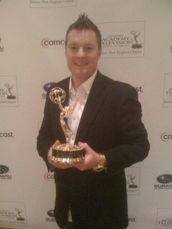 New England sports personality Charlie Moore holding a New England Emmy Award in 2011