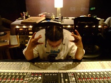 Hip hop producer Chilly Chill behind a large audio console in a recording studio.