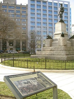 Admiral David G. Farragut (Ream statue), crafted in 1881 from the propeller of his flagship, stands in Farragut Square in downtown Washington, D.C. The National Park Service interpretive plaque in the foreground prominently quotes his famous order.